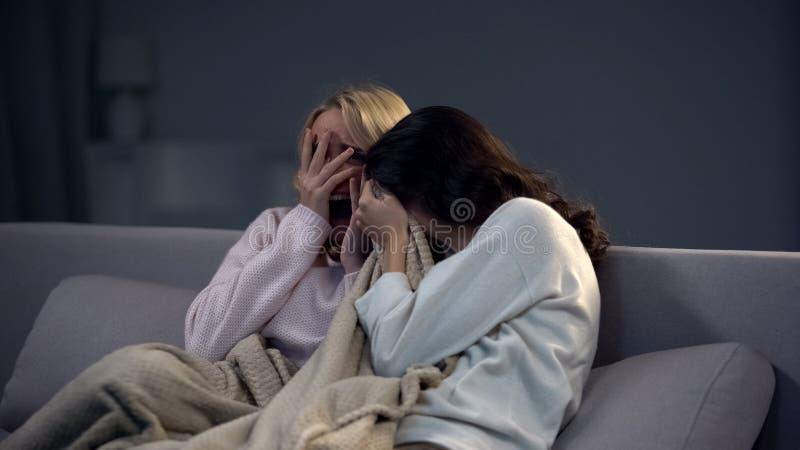 Two beautiful scared girls watching horror movie at night, frightening episode stock photo