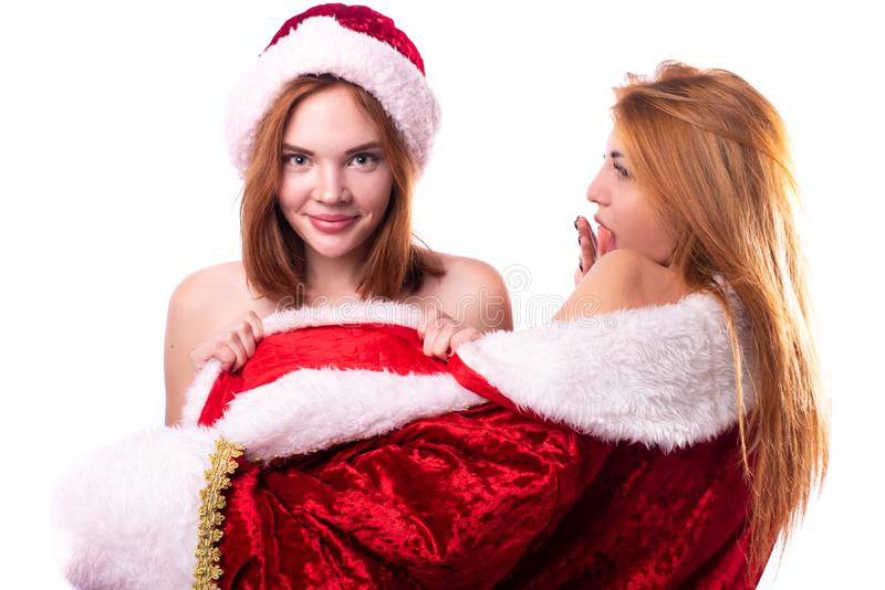 Two beautiful girls with red hair in mittens and Santa Claus hat royalty free stock photo