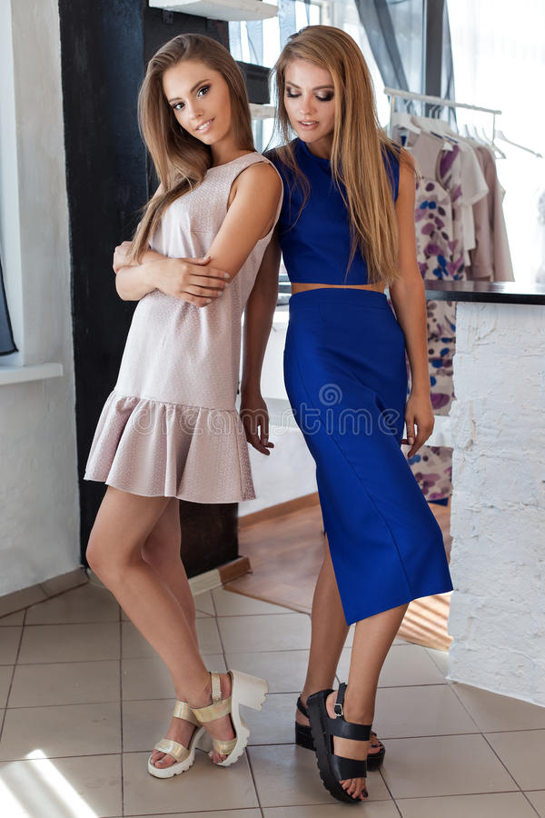Two beautiful young women friends in beautiful fashion dress in the studio posing for the camera stock image