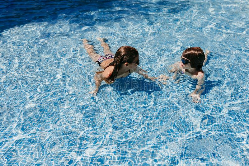 Two beautiful sister kid girls swimming at the pool with modern sunglasses. fun outdoors. Summertime and lifestyle concept royalty free stock photos