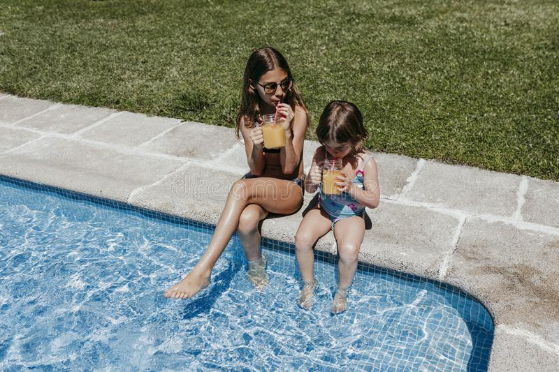Two beautiful sister kids at the pool drinking healthy orange juice and having fun outdoors. Summertime and lifestyle concept stock photography