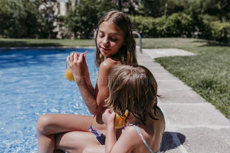 Two beautiful sister kids at the pool drinking healthy orange juice and having fun outdoors. Summertime and lifestyle concept royalty free stock photo