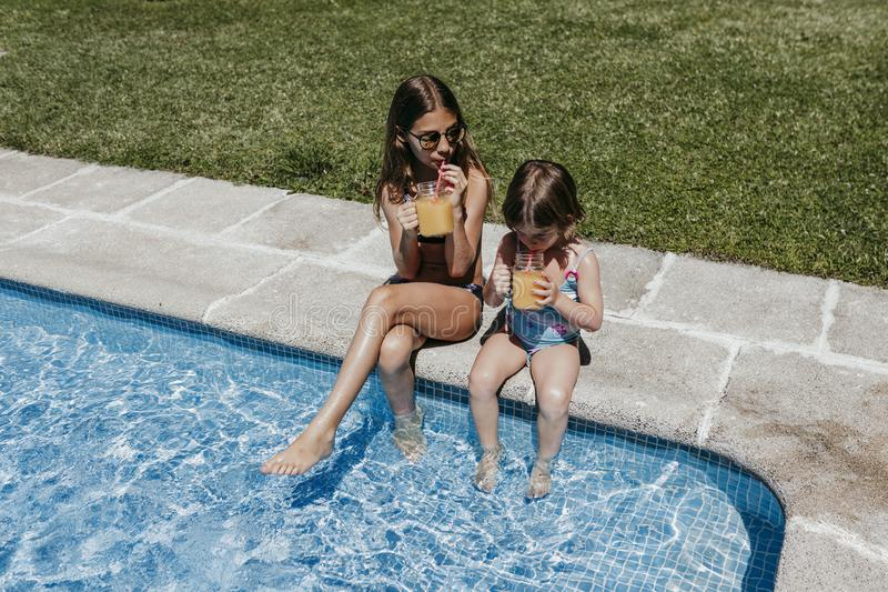 Two beautiful sister kids at the pool drinking healthy orange juice and having fun outdoors. Summertime and lifestyle concept stock photos