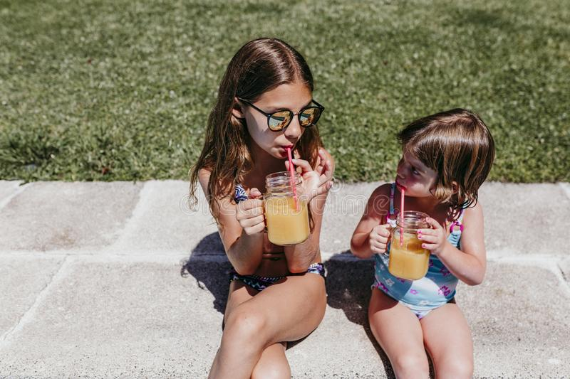 Two beautiful sister kids at the pool drinking healthy orange juice and having fun outdoors. Summertime and lifestyle concept stock image