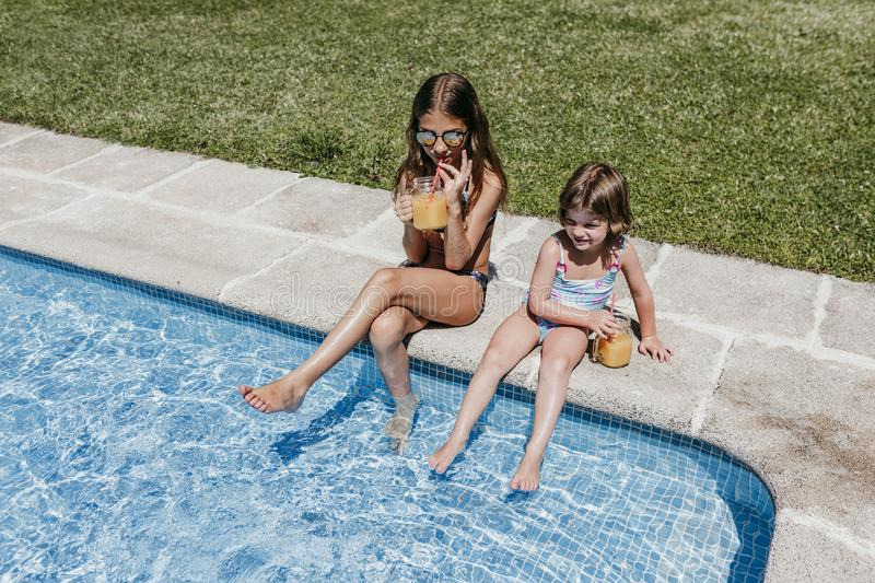 Two beautiful sister kids at the pool drinking healthy orange juice and having fun outdoors. Summertime and lifestyle concept. Childhood, playful, blue stock photography