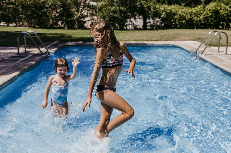 Two beautiful sister kids at the pool playing, running and having fun outdoors. Summertime and lifestyle concept stock photo