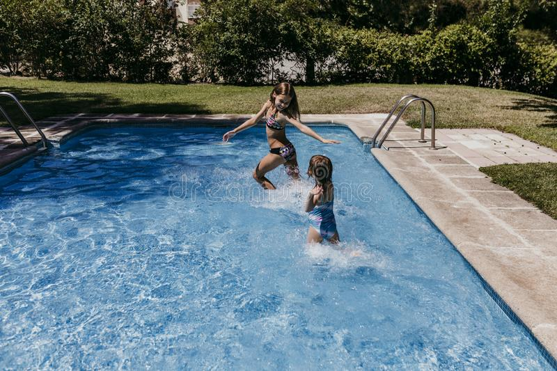 Two beautiful sister kids at the pool playing, running and having fun outdoors. Summertime and lifestyle concept stock photography