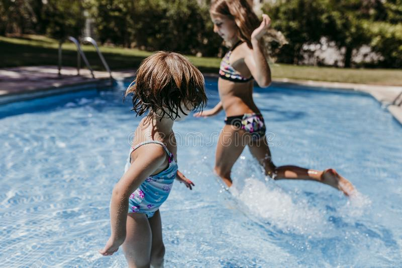 Two beautiful sister kids at the pool playing, running and having fun outdoors. Summertime and lifestyle concept royalty free stock photo