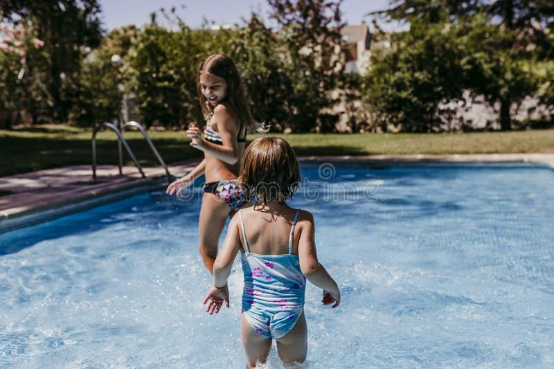 Two beautiful sister kids at the pool playing, running and having fun outdoors. Summertime and lifestyle concept stock photos