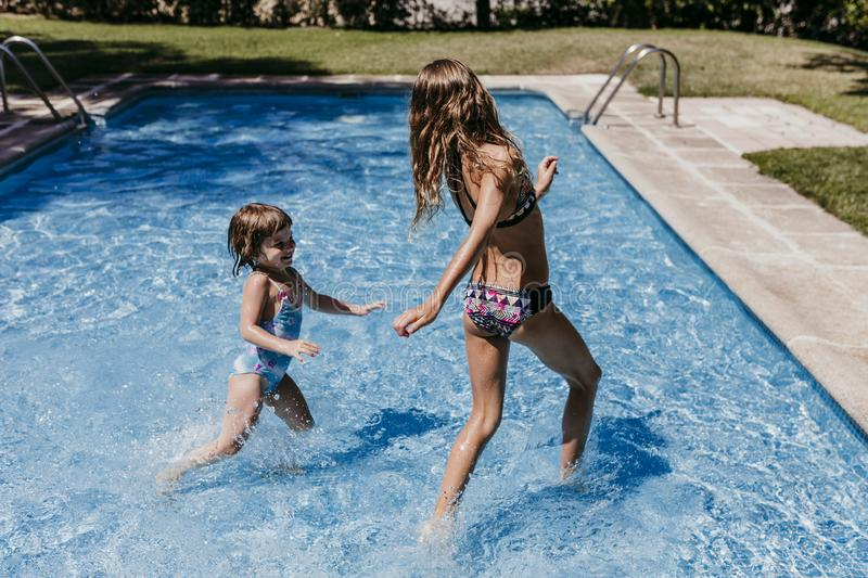Two beautiful sister kids at the pool playing, running and having fun outdoors. Summertime and lifestyle concept stock image