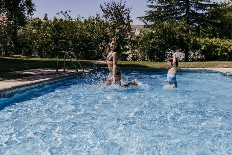Two beautiful sister kids at the pool playing, running and having fun outdoors. Summertime and lifestyle concept royalty free stock photography
