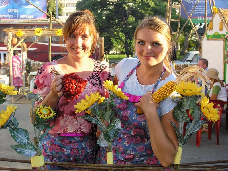 Two beautiful smiling Caucasian country women show agricultural products produced on their farm at Russian International Economic. Sochi, Russia - September 28 royalty free stock photography
