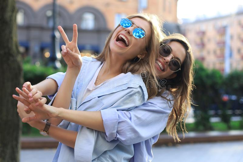 Two beautiful smiling girls in trendy summer clothes posing on street background. Models are having fun and hugging royalty free stock images