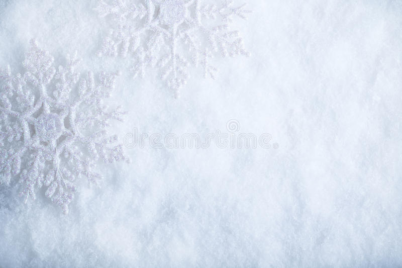Two beautiful sparkling vintage snowflakes on a white frost snow background. Winter and Christmas concept stock photography