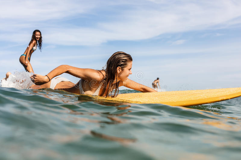 Two beautiful sporty girls surfing in the ocean. stock image