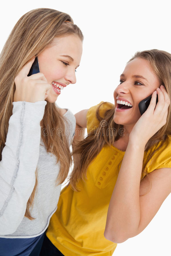 Two beautiful students laughing on the phone royalty free stock images