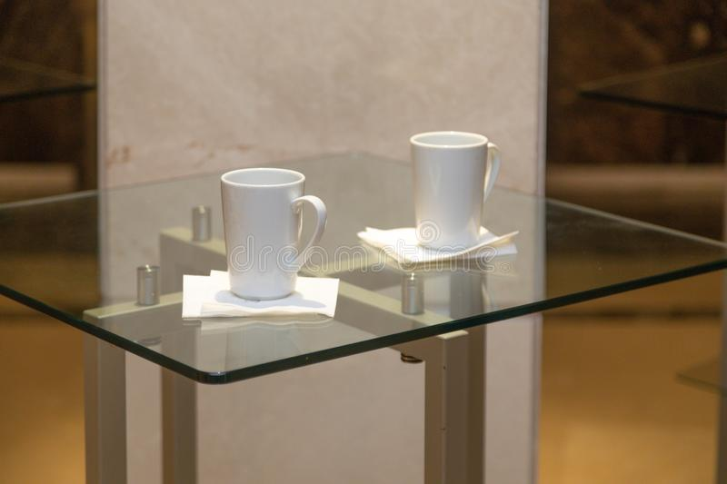 Two white cups on the glass table stock image
