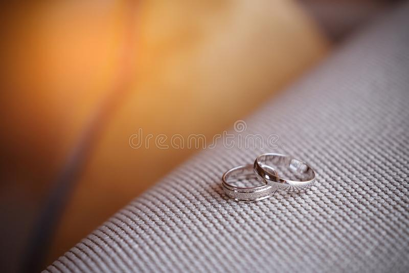 Two beautiful white gold engagement rings with diamond stones lie on the fabric with a rough texture. Wedding ring.  stock photos