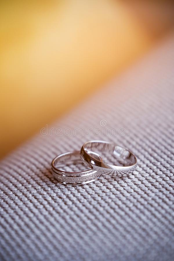 Two beautiful white gold engagement rings with diamond stones lie on the fabric with a rough texture. Wedding ring.  stock photo