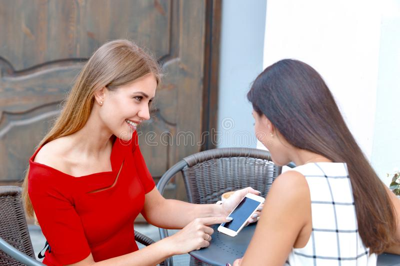 Woman shows on a mobile phone something to his girlfriend. Two beautiful woman drinking coffee at outside bar. Woman shows on a mobile phone something to his stock images