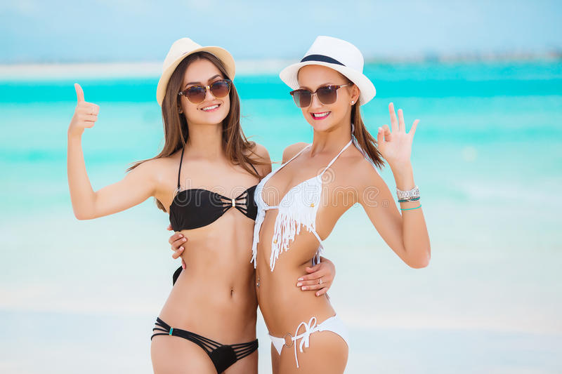 Two beautiful women in bikini and fashionable hats. Two beautiful young women,brunette in sun glasses,beautiful figure,dressed in a bikini black and white color stock image