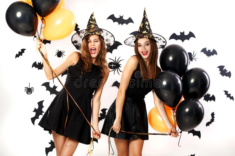 Two beautiful women in black dresses and witch hats have fun with black and orange balloons. Halloween party stock photography