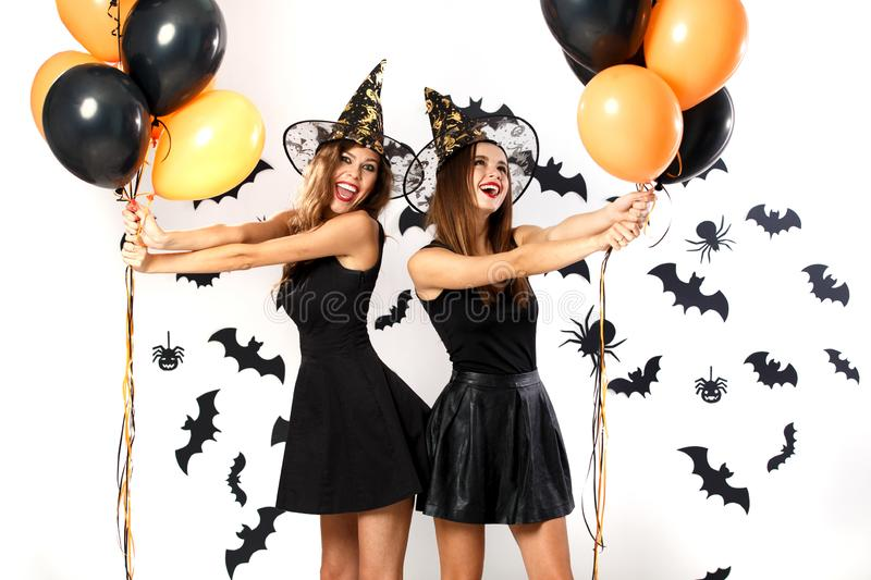 Two beautiful women in black dresses and witch hats have fun with black and orange balloons. Halloween party stock photo