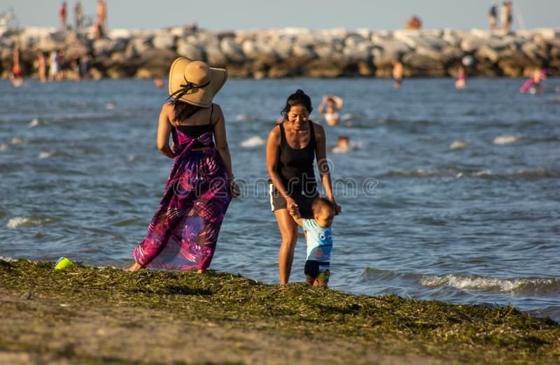 Two beautiful women with a child having fun, the women relax on the shore and watch the bathers taking a walk. royalty free stock photography