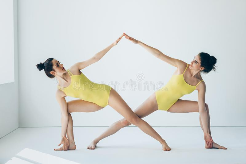 Two beautiful women doing yoga asana extended side angle pose. Two young beautiful women doing yoga asana extended side angle pose Utthita Parsvakonasana stock photos