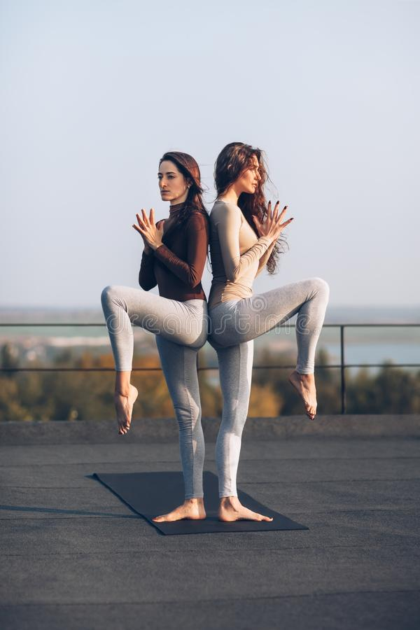 Two beautiful women doing yoga asana on the roof outdoors royalty free stock images