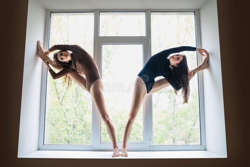 Two beautiful women doing yoga asana on window sill stock images