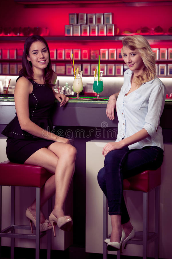 Two beautiful women drinking cocktail in a night club and having stock photo