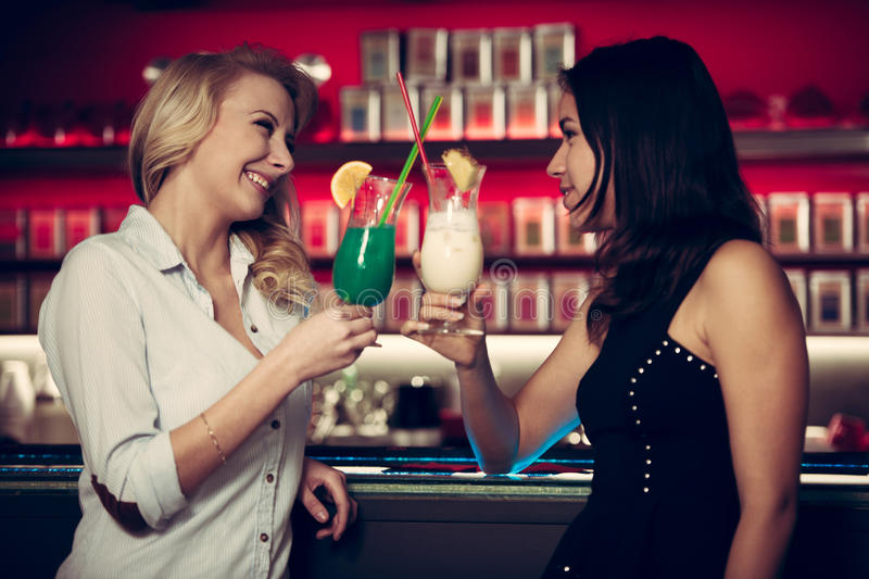 Two beautiful women drinking cocktail in a night club and having stock photos