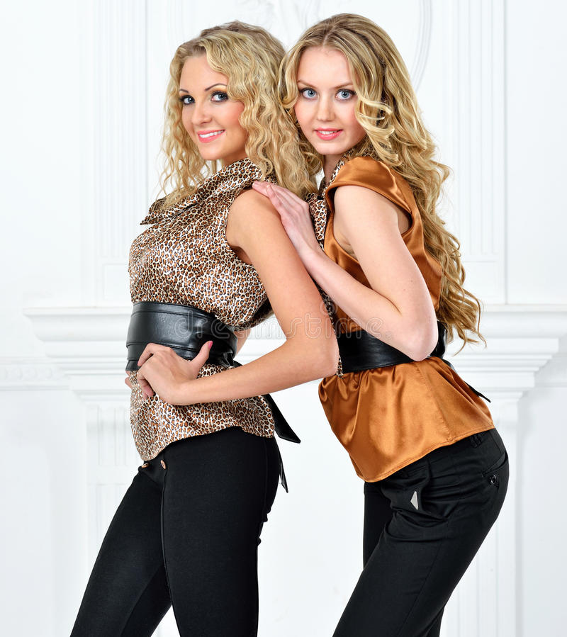 Two beautiful women in elegant evening suit. stock photography