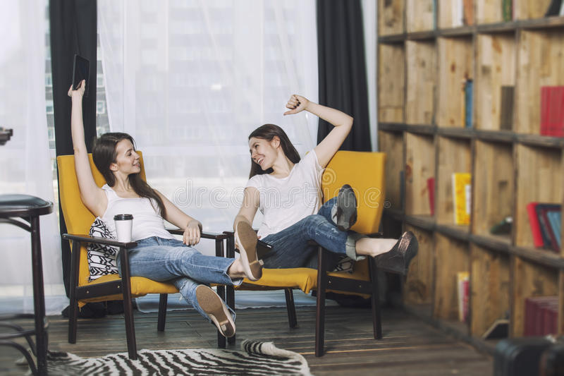 Two beautiful women friends talking happy smiles at home stock photography