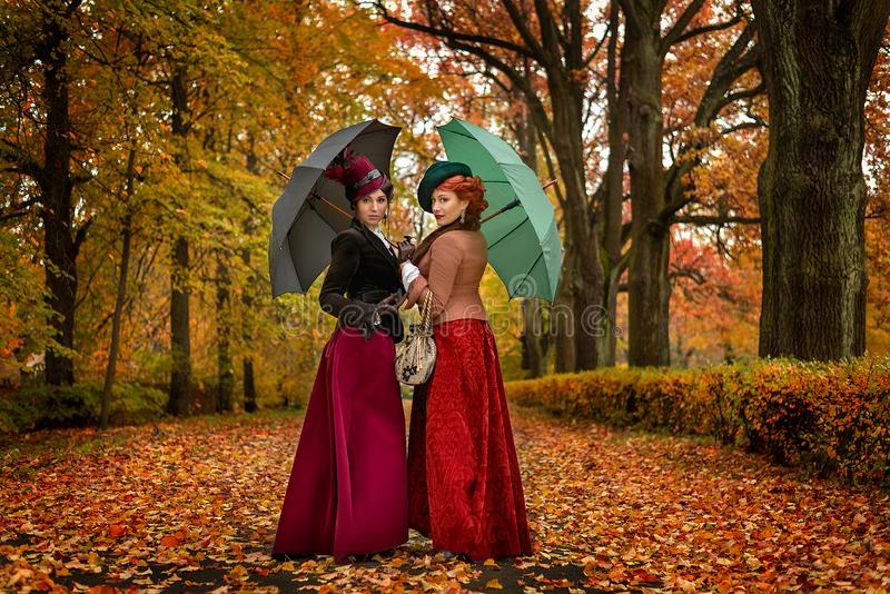 Two beautiful women with umbrellas in the park stock photography