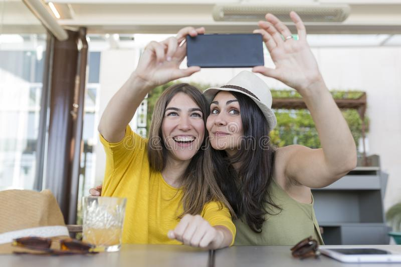 Two beautiful women having breakfast in a restaurant and taking a selfie with mobile phone. They are laughing. Indoors lifestyle royalty free stock photo