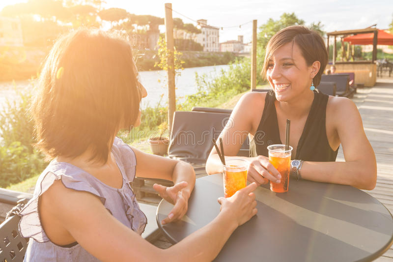 Two beautiful women having a cocktail outdoor at sunset stock image