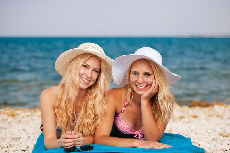 Two women having fun on beach in summer royalty free stock images