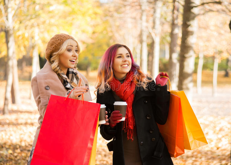 Two beautiful women having a relaxing conversation with coffee. After shopping walking in the autumn park royalty free stock photos