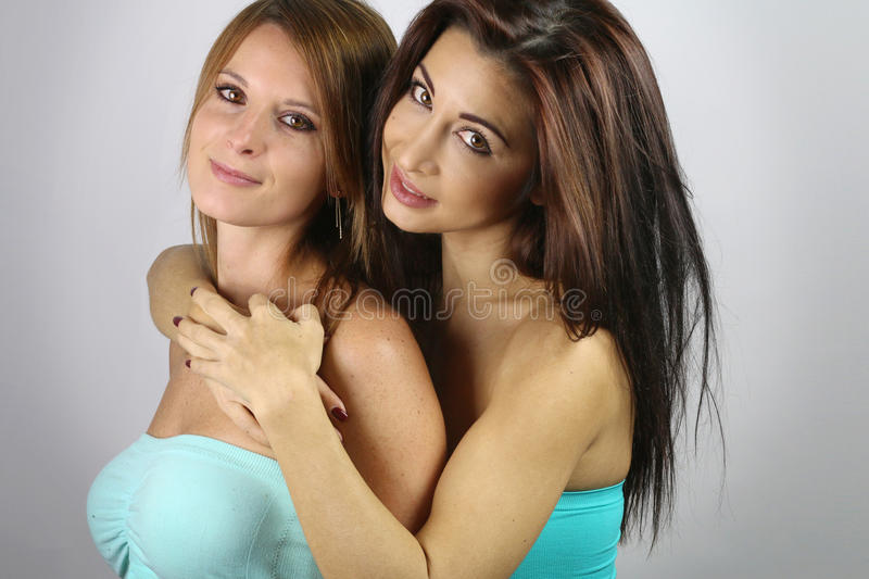 Two beautiful women hugging. Over a gray background royalty free stock images