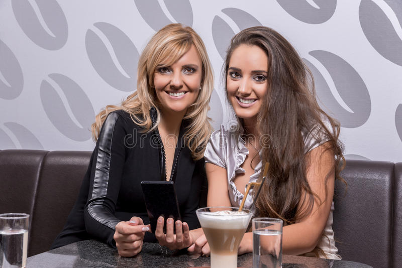Two beautiful women laughing over a coffee stock image