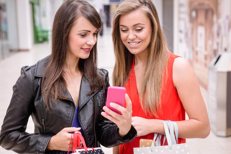 Two beautiful women looking at phone in shopping mall royalty free stock images