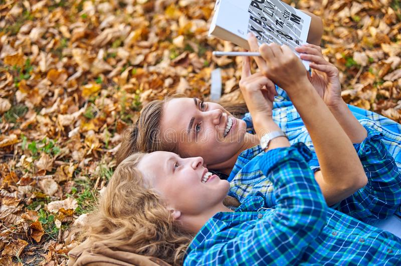 Two beautiful women lying on leaves and reading books in autumn park. Education, friendship lifestyle concept stock photo