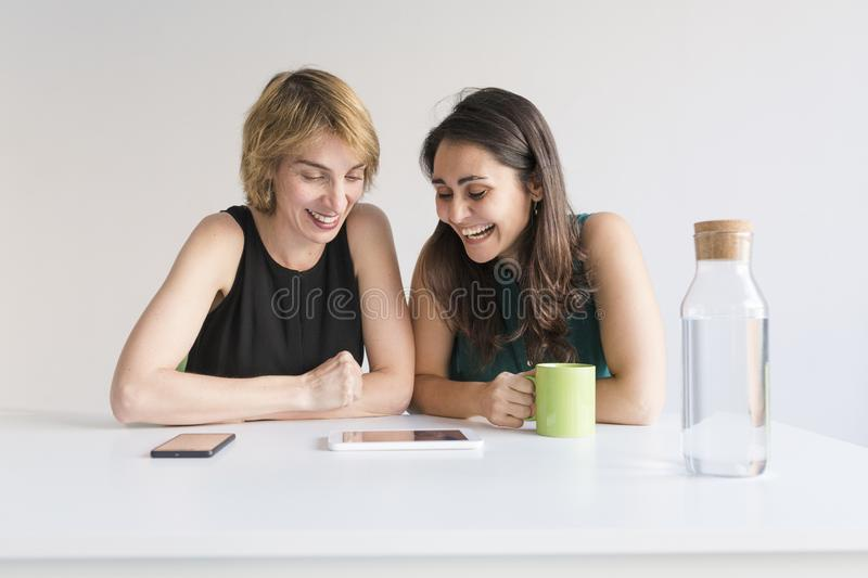 Two beautiful women at the office searching for information on tablet or mobile phone. White background. Modern office concept. royalty free stock photo