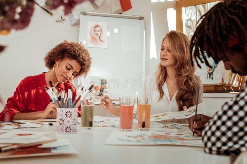Two beautiful women and one man attending painting classes. Painting classes. Two beautiful women and one men feeling excited while attending painting classes stock photo