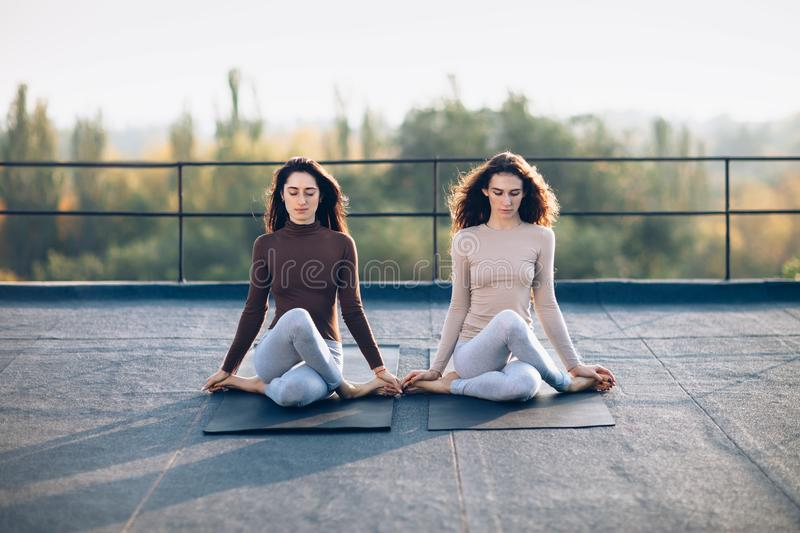 Two beautiful women perform meditative pose gomukhasana. On the roof outdoor. Young attractive girls sit quietly in a relaxation pose. Concentration, healthy royalty free stock image
