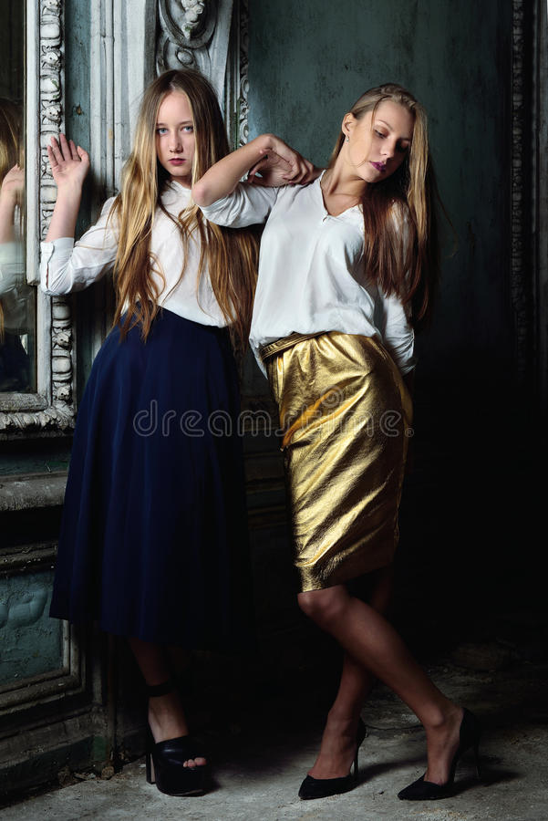 Two beautiful women posing in obsolete interior. stock image