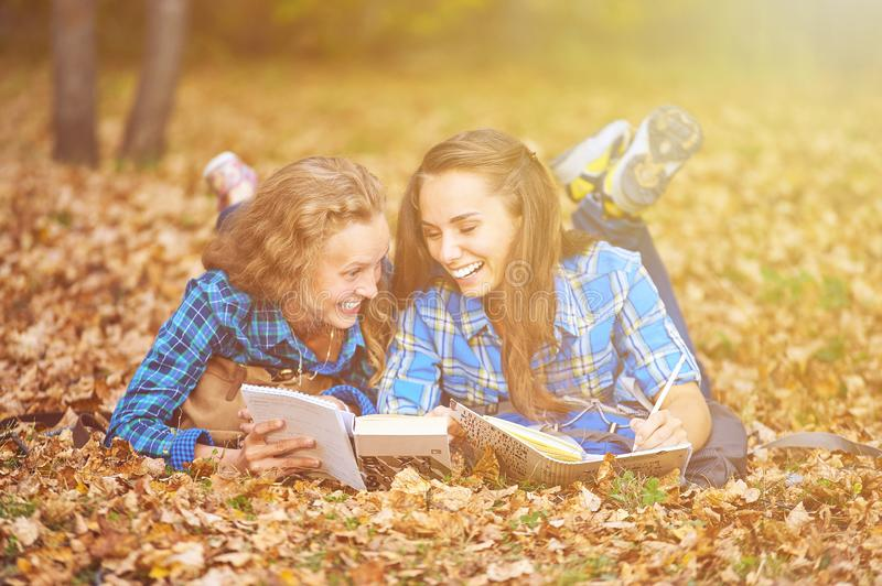 Two beautiful women lying on leaves and reading books in autumn park. Education, friendship lifestyle concept royalty free stock photography