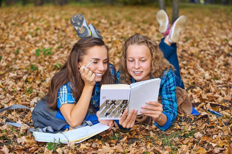Two beautiful women lying on leaves and reading books in autumn park. Education, friendship lifestyle concept royalty free stock images